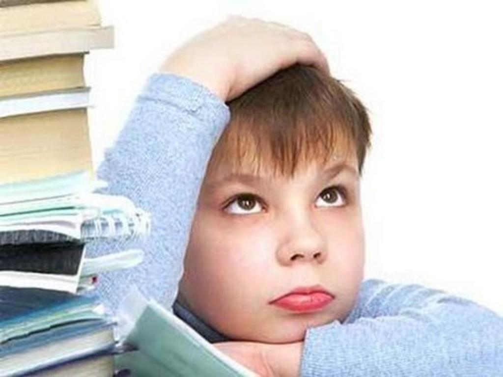 Мальчик. Младший школьник заваленный учебниками