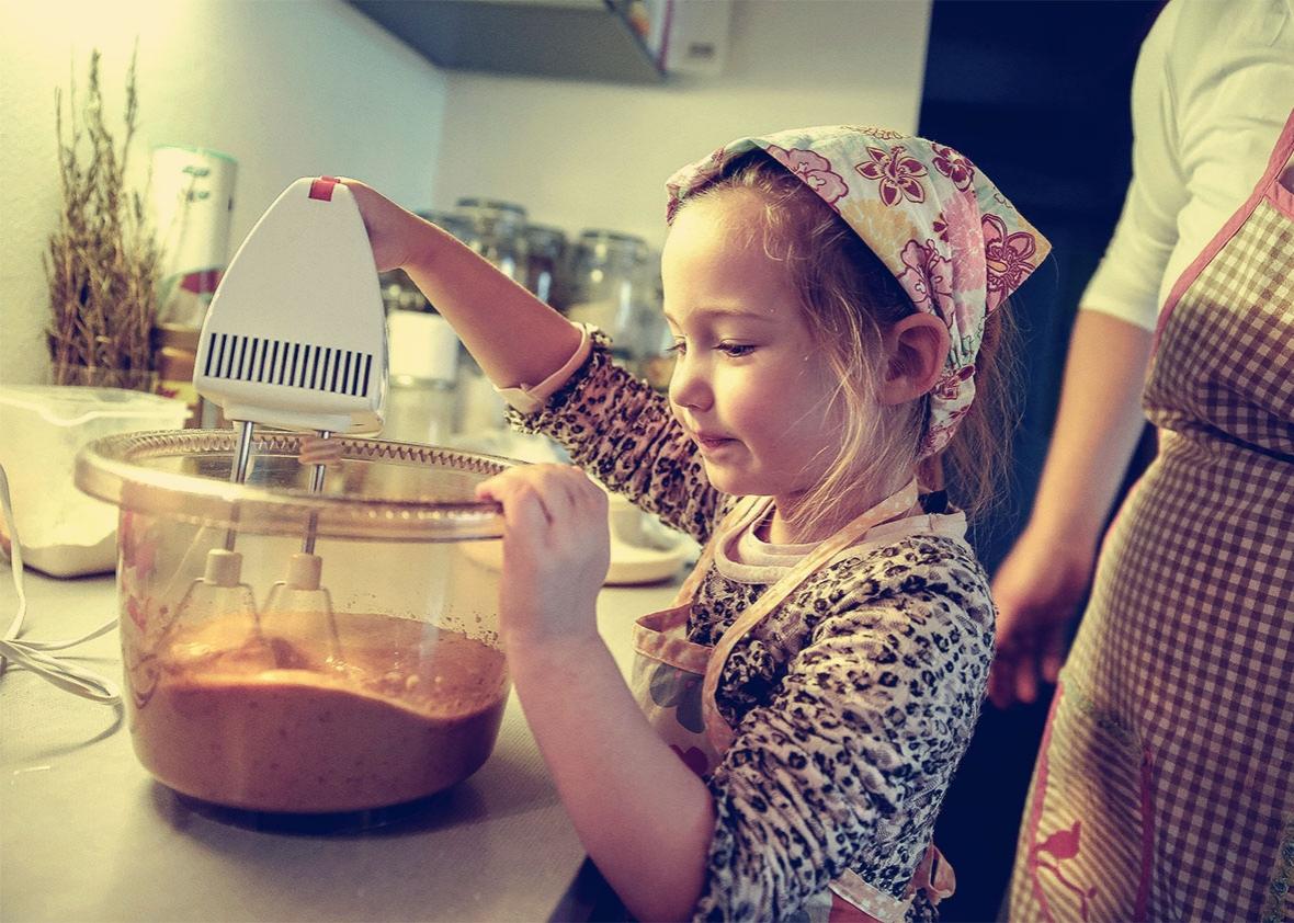 Девчка помогает маме готовить