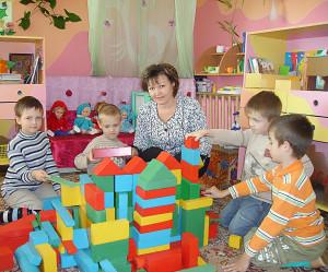 Воспитатель с детьми строит замок из кубиков