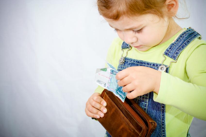 Девочка берет деньги из кошелька