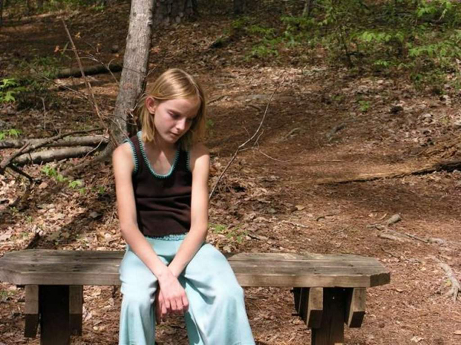 Девочка сидит на лавке