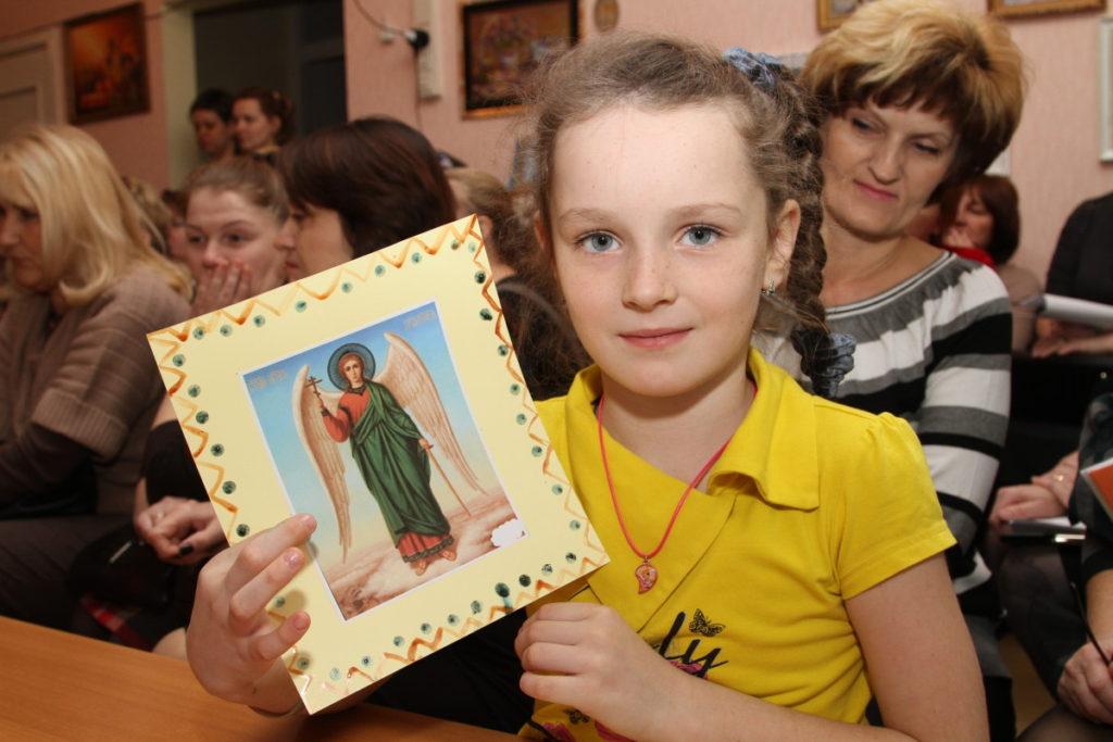 Девочка держит рисунок