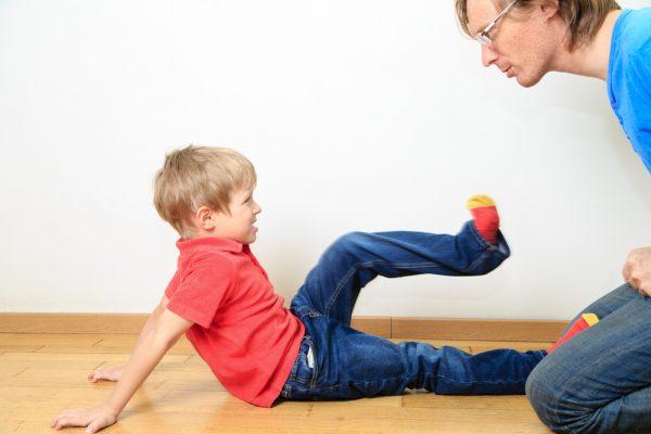 Мальчик в красной футболке бьет папу ногами