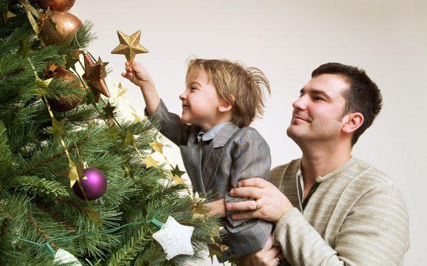 Папа с сыном украшают новогоднюю елку