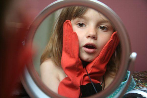 Девочка в красных перчатках смотрит в зеркало