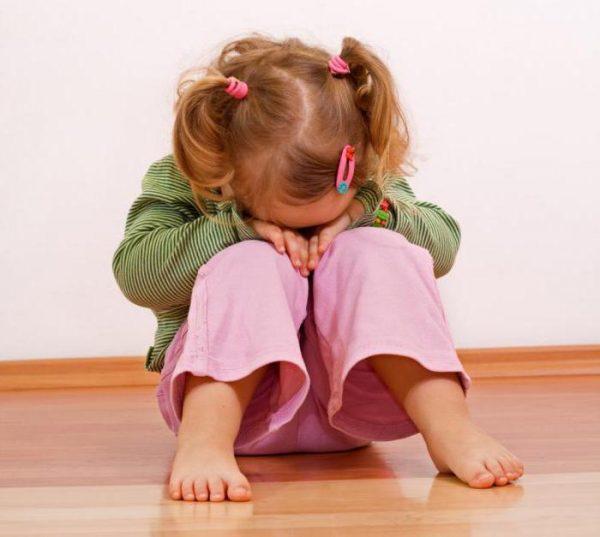 Девочка сидит на полу и плачет