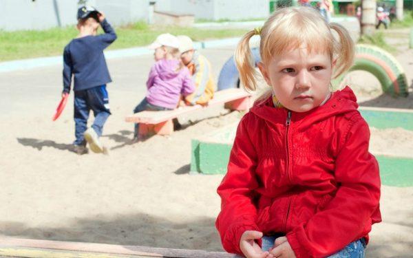 Девочка сидит одна у песочницы