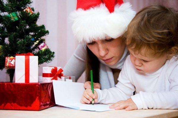 Ребенок с мамой пишут письмо Деду Морозу