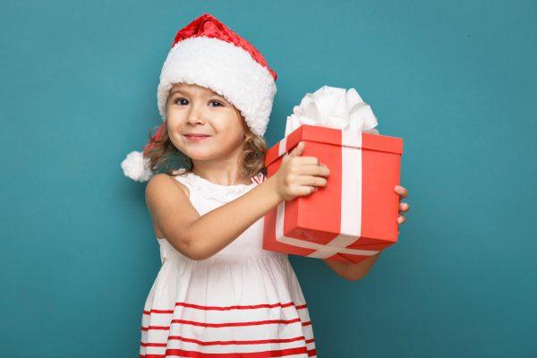 Девочка в белом платье с красной шапочкой с подарком