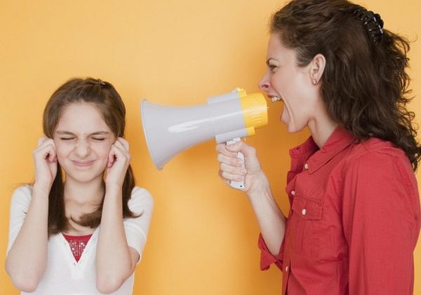 Мама держит рупор и кричит на доч, которая прикрывает уши