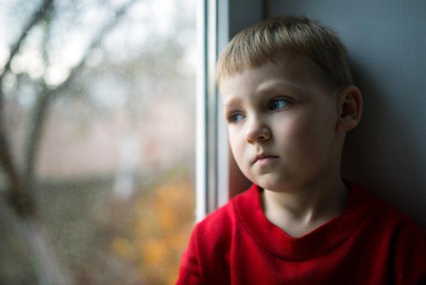Мальчик сидит на подоконнике и грустит