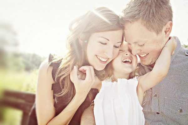 Родители обнимают дочь