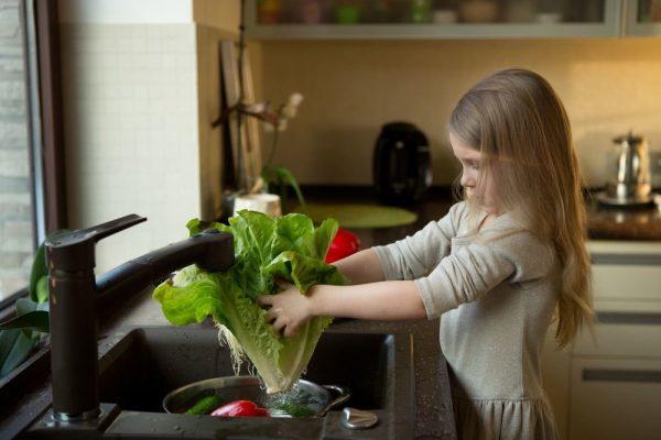 девочка моет овощи под проточной водой