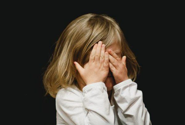 Девочка закрыла лицо руками и плачет