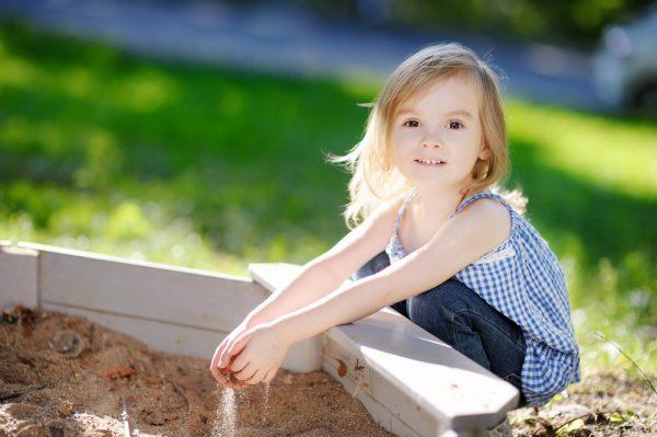 Девочка играет возле песочницы
