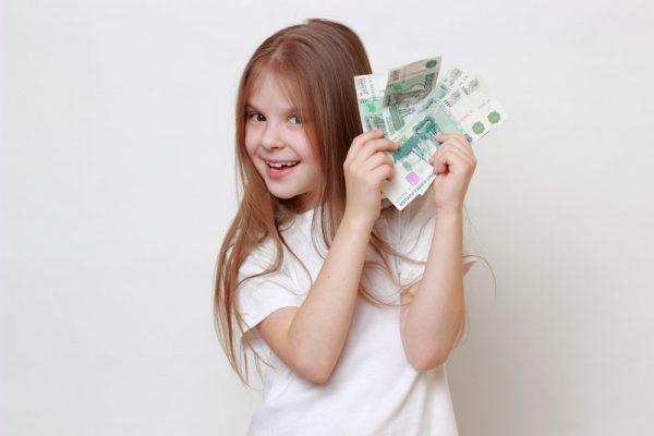 девочка держит в руках много тысячных купюр