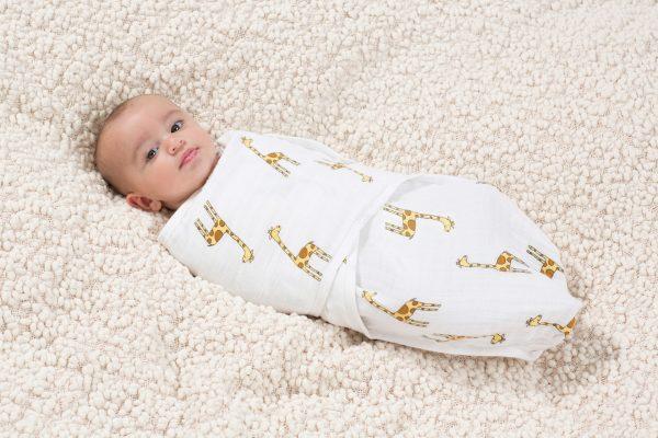 Грудной ребенок в пеленке с жирафами
