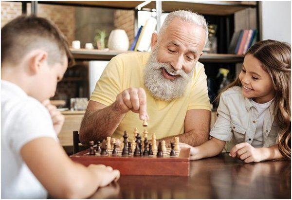 Дедушка учит внуков играть в шахматы