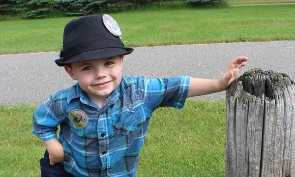 Мальчик в синей рубашке и черной шляпе улыбается
