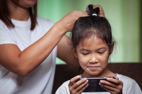 Девочка сидит в телефоне, пока мама делает ей прическу