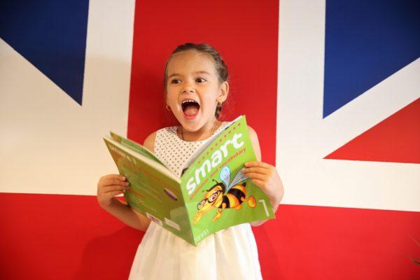 Ребенок держит в руках учебник по английскому языку