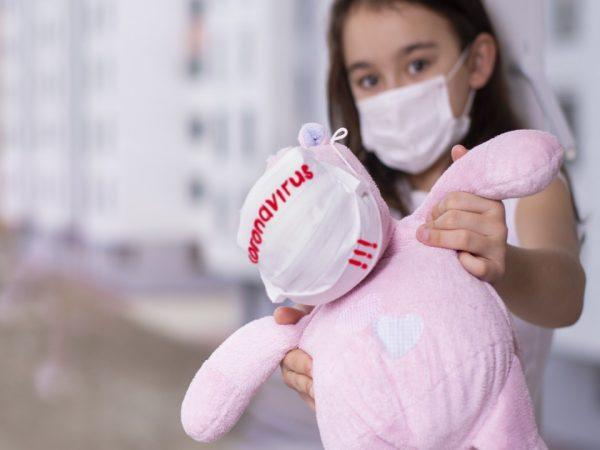 Девочка с розовой игрушкой в защитной маске