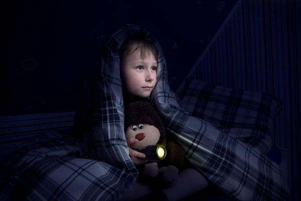 Ребенок накрылся одеялом и держит в руках мишку