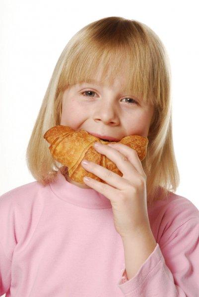 Девочка ест круассан