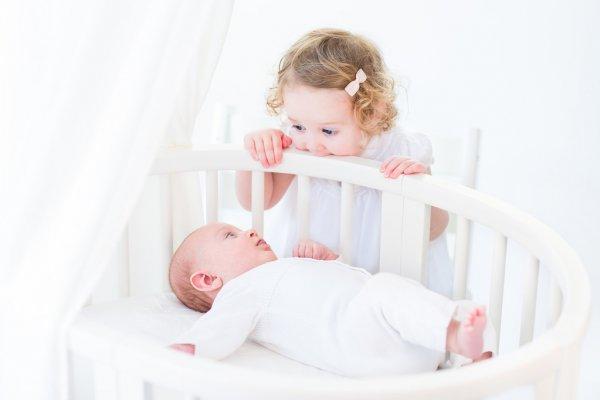 Маленькая девочка смотрит на малыша в кроватке