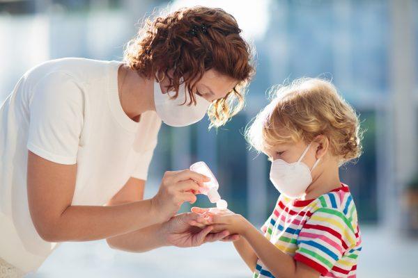 Мама обрабатывает руки ребенку и надевает себе и мальчику защитную маску
