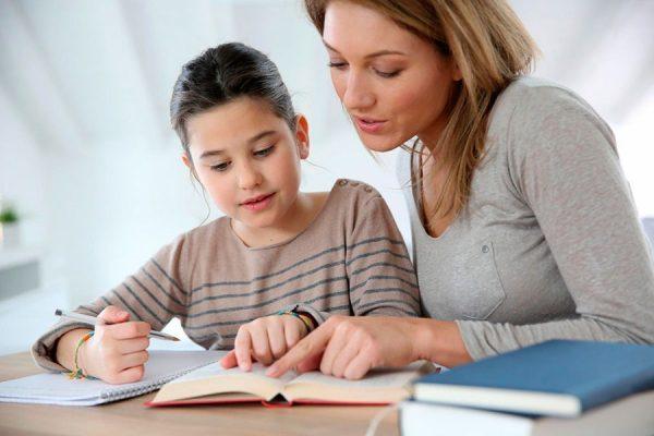 Мама помогает дочке делать уроки