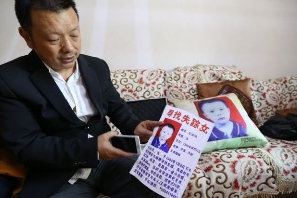 Отец держит объявление о пропаже дочери