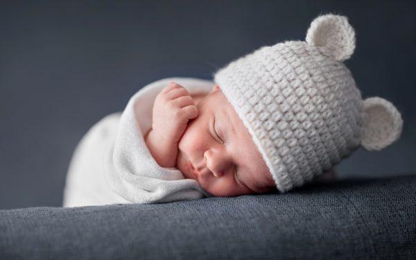 Ребенок спит в вязаной шапочке