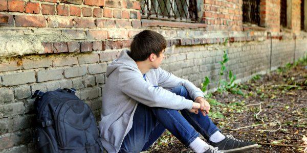Одинокий и расстроенный подросток сидит возле кирпичной стены