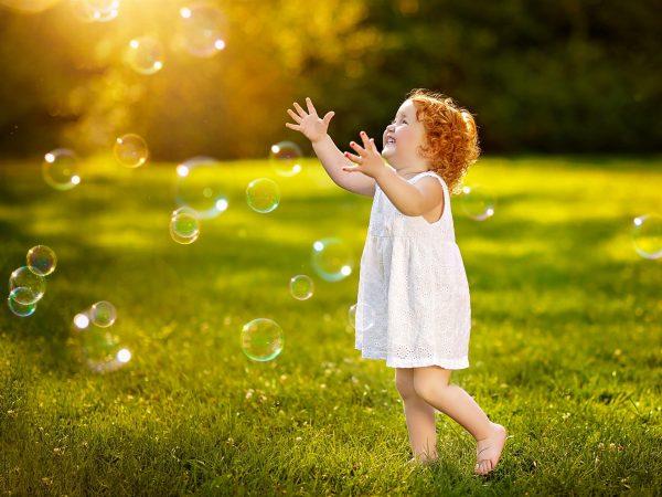 Девочка играет с мыльными пузырями