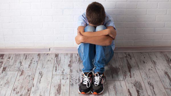 Мальчик расстроен и сидит на полу, прижавшись лицом к коленкам