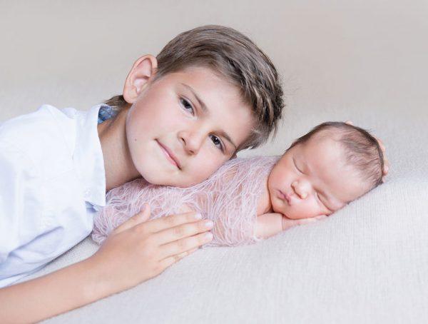 Мальчик обнимает новорожденного ребенка