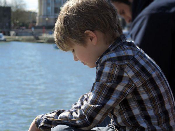 Мальчик возлу озера в клетчатой рубашке грустит