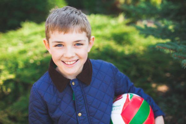 Мальчик в синей куртке с мячиком в руках улыбается
