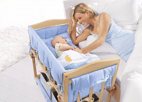 Малыш лежит в приставной кроватке рядом с мамой