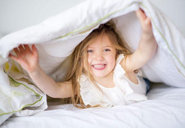 Девочка веселится в кровати