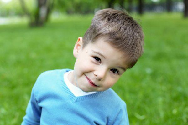 Мальчик в синей кофте кривляется