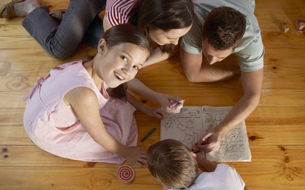 Мама, папа, сын, дочь разукрашивают на полу