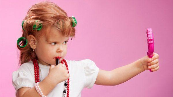Девочка на розовом фоне смотрится в зеркало, держа в руках помаду