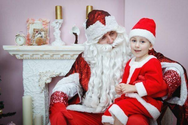 Ребенок сидит на коленках Деда Мороза