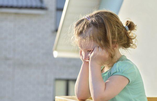 Девочка в зеленой футболке грустит на улице