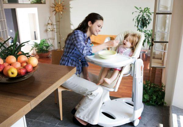 Мама кормит малыша на стульчике для кормления