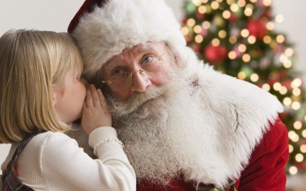 Ребенок нашептывает желание Деду Морозу на ушко