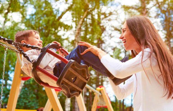 Мама качает ребенка на качелях