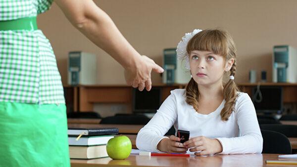 Учительница хочет забрать мобильный у ученицы
